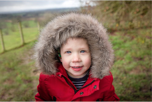 child in a field wearing a red coat