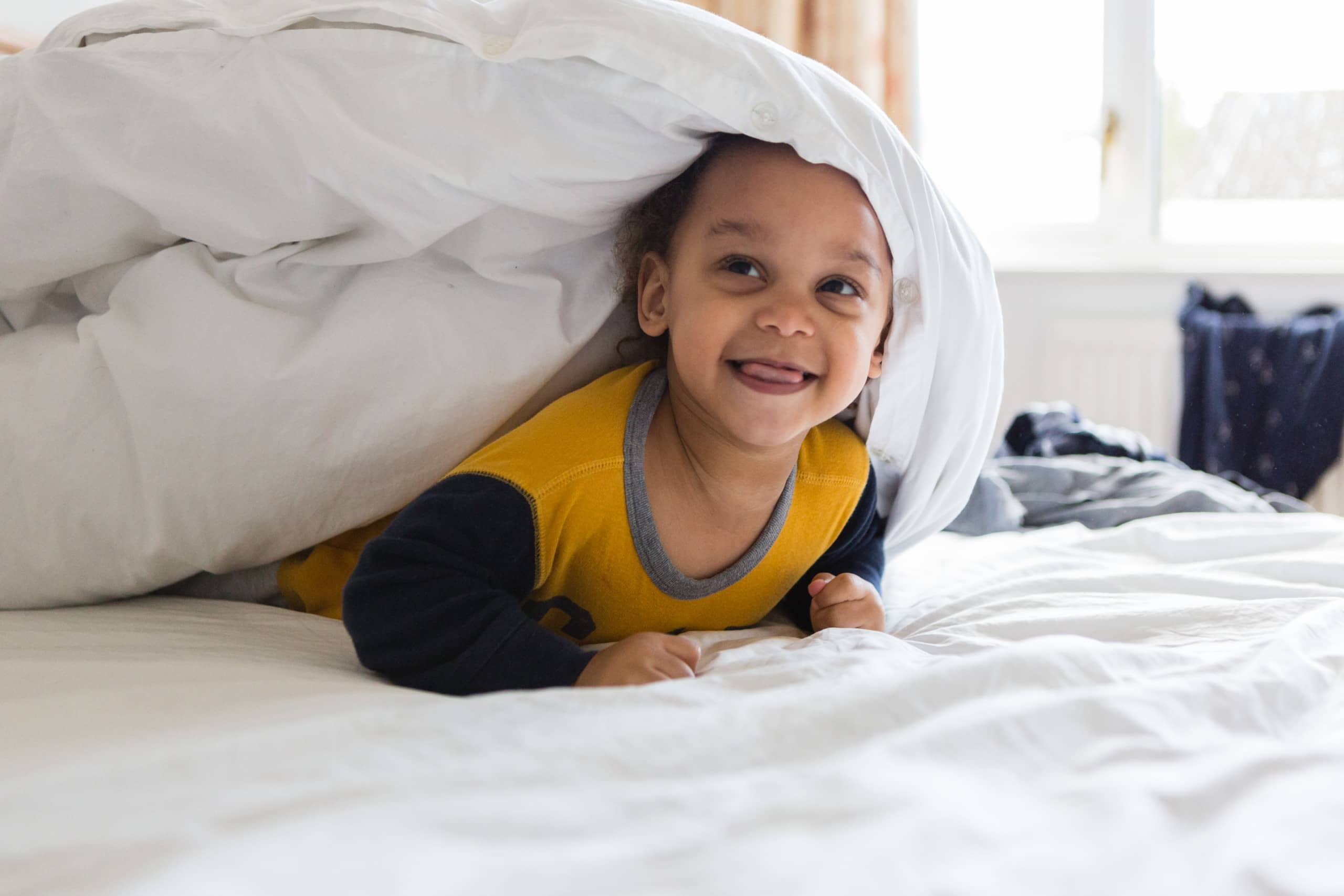 Young boy plays under duvet on bed
