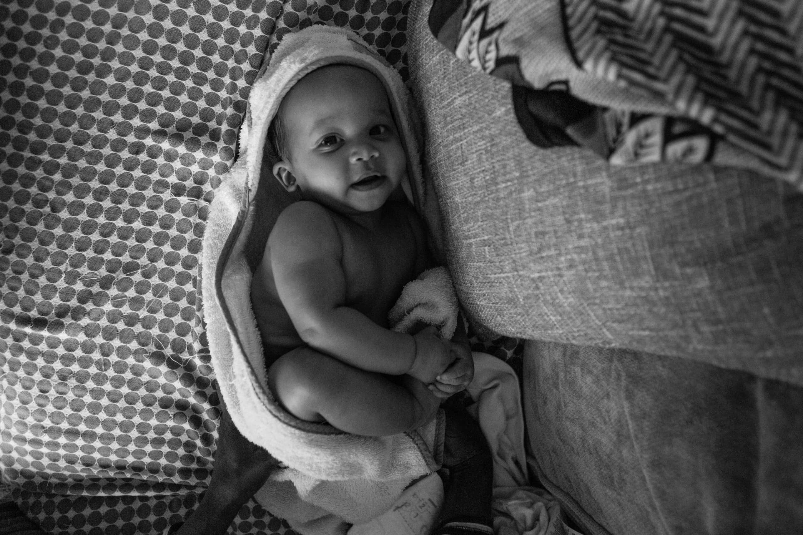 Young baby in towel looks up at the camera