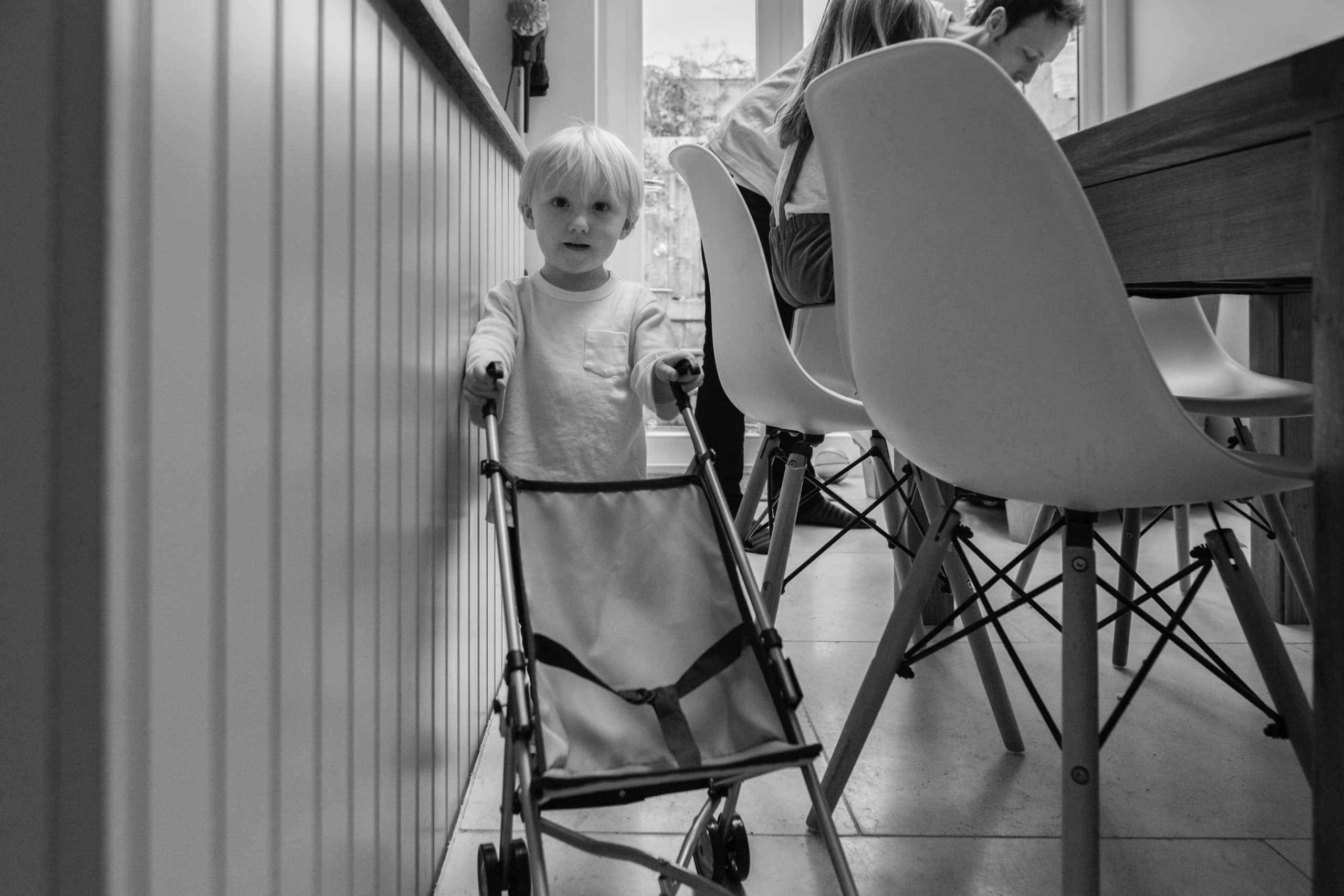 Young boy plays with push chair