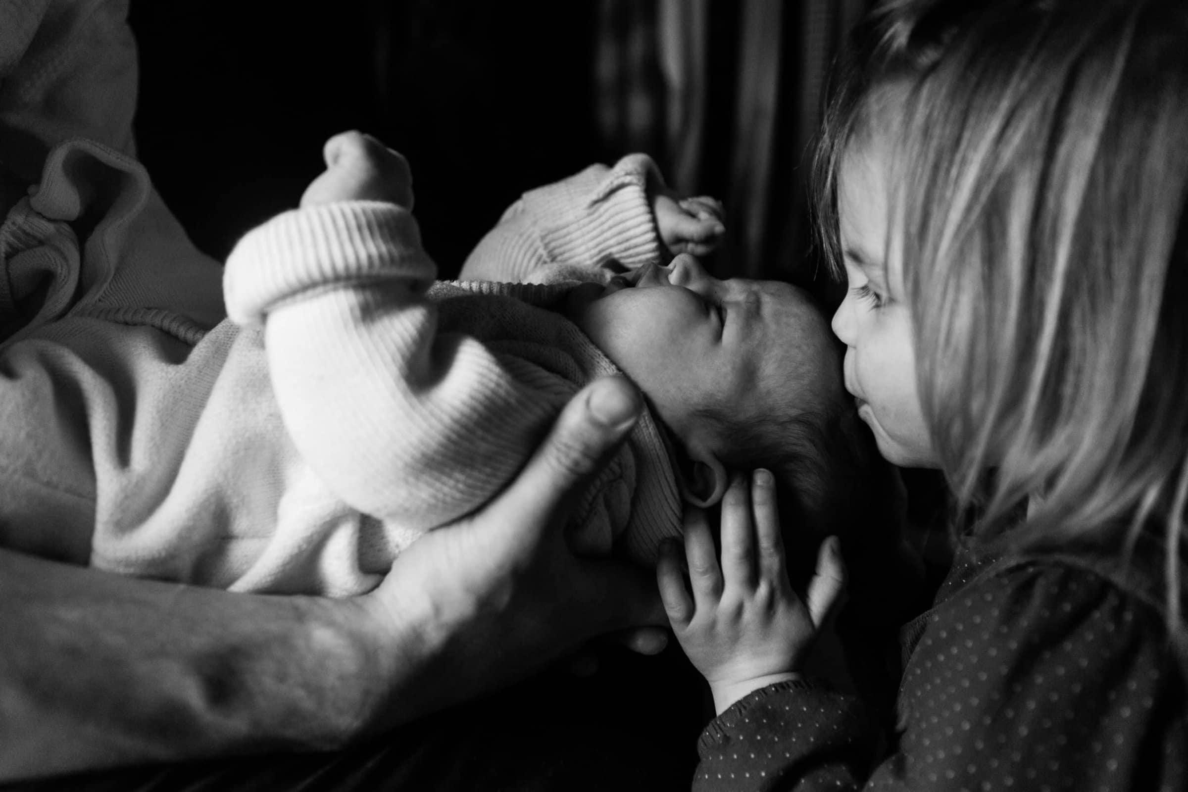 Older sister kisses baby sister | Newborn Photographer Bath