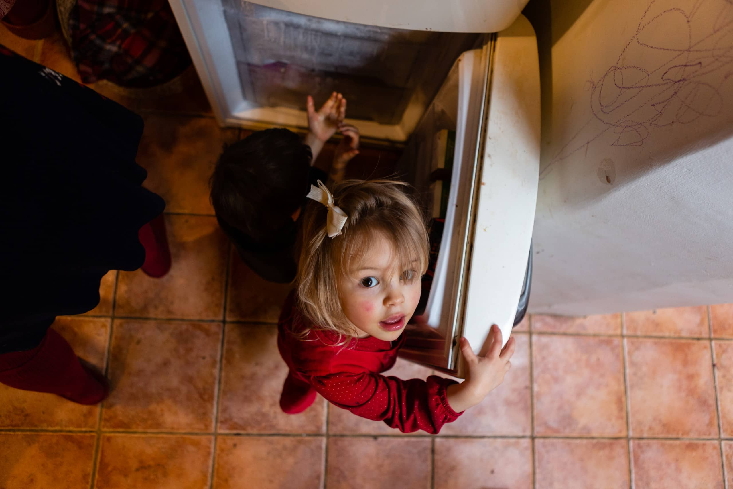 Children caught in the act of eat ice from freezer
