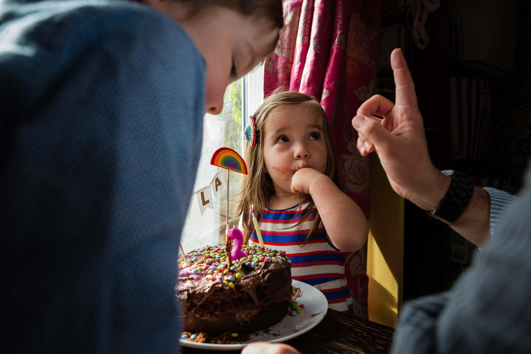 Little girl being told not to stick fingers in her cake - Family Photographer Bath