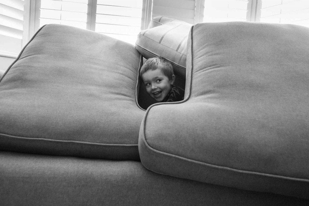 Little boy peeking out of sofa - Family Photographer Bath