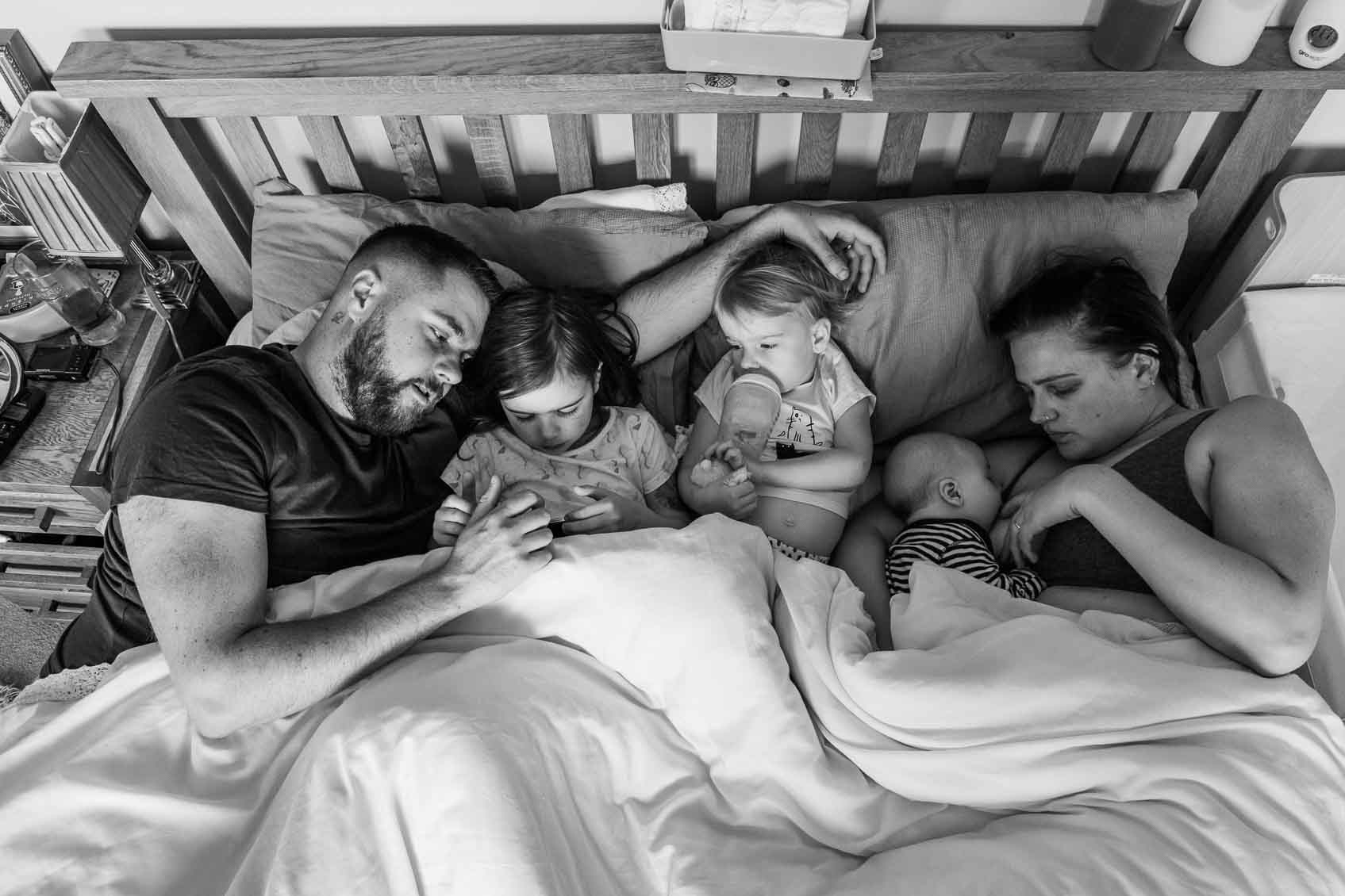 Family snuggles in bed