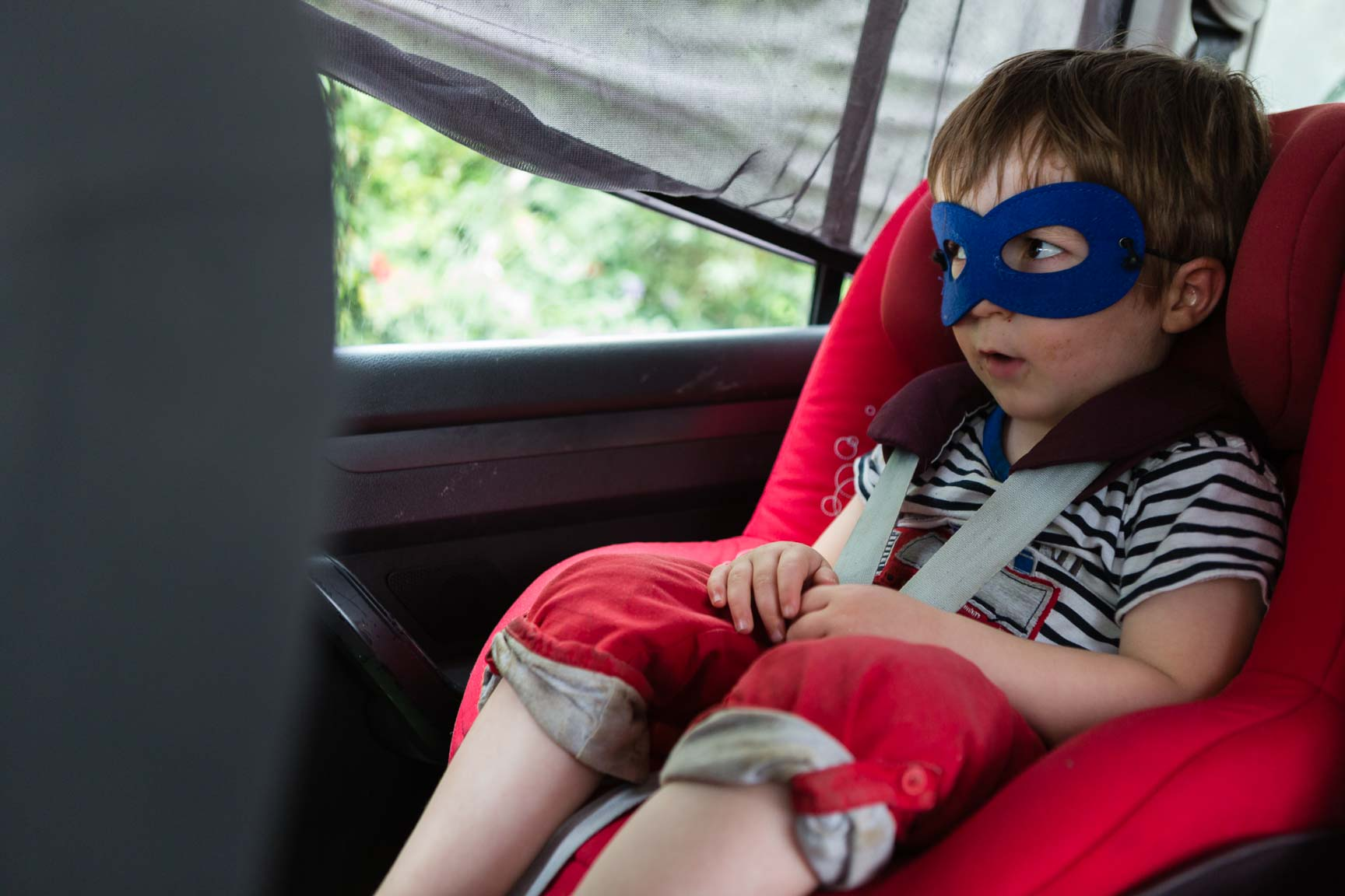 Little boy in car seat with superhero mask