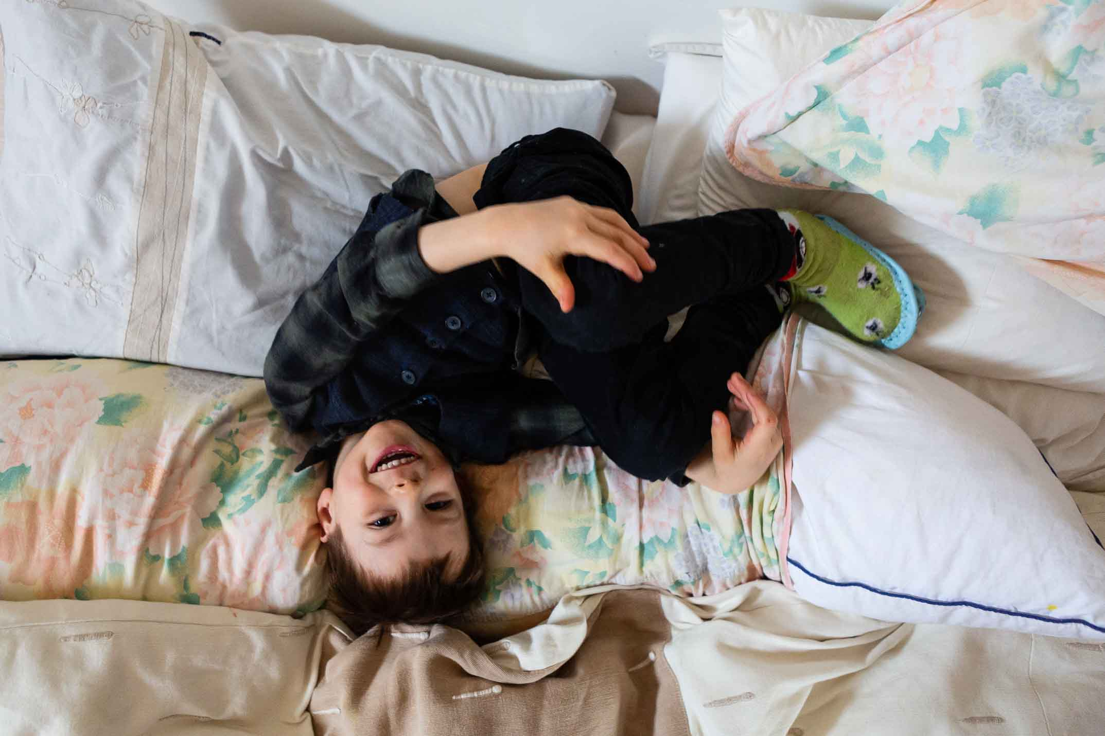Boy curled up on the bed | Somerset Family Photography