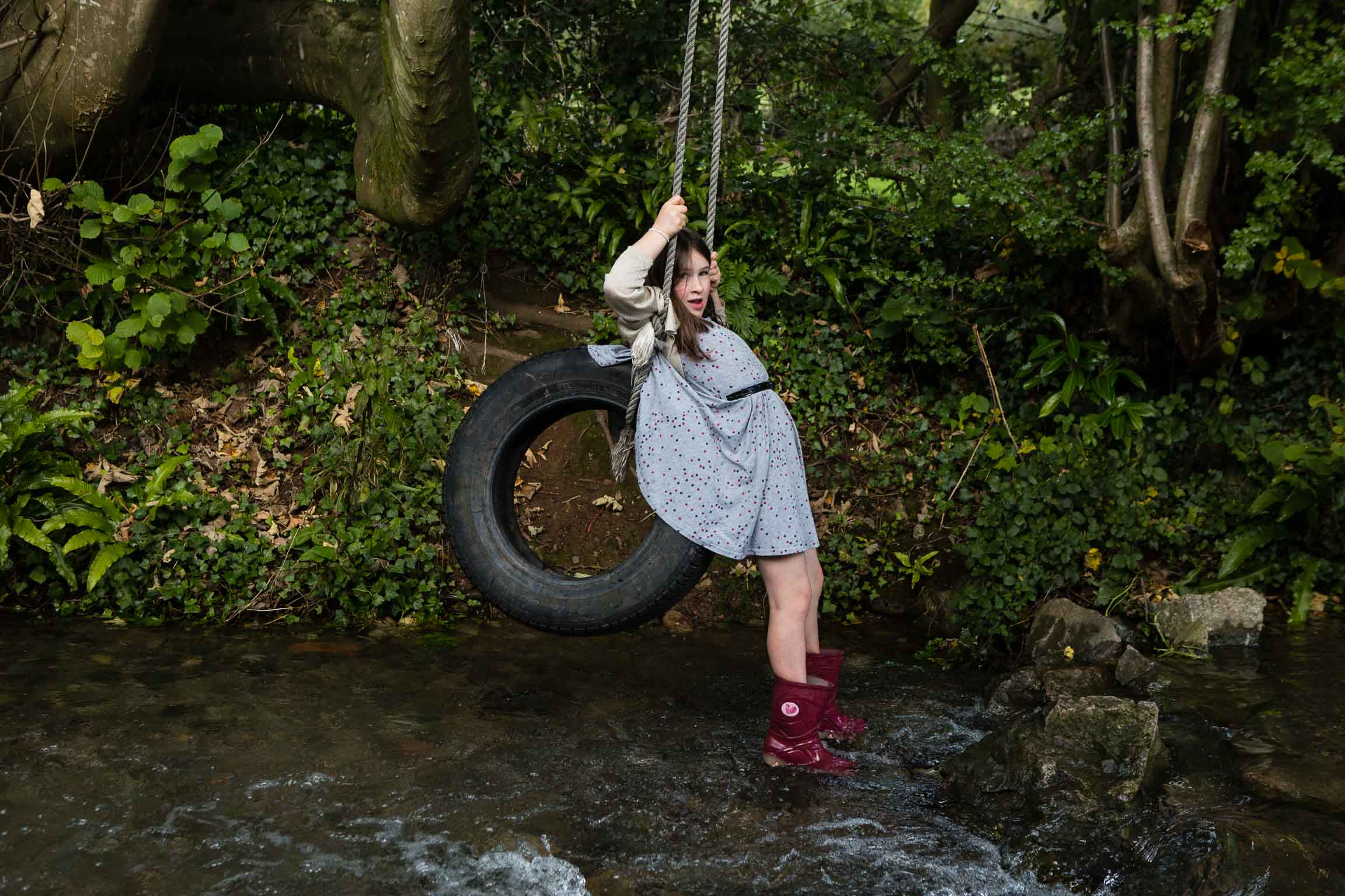 Little girl dangling from tyre swing in river | Bath Family Photographer
