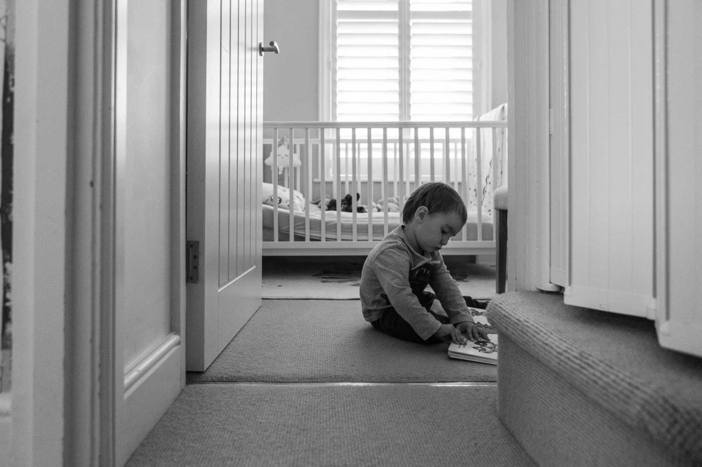 Young boy reading a book in a doorway