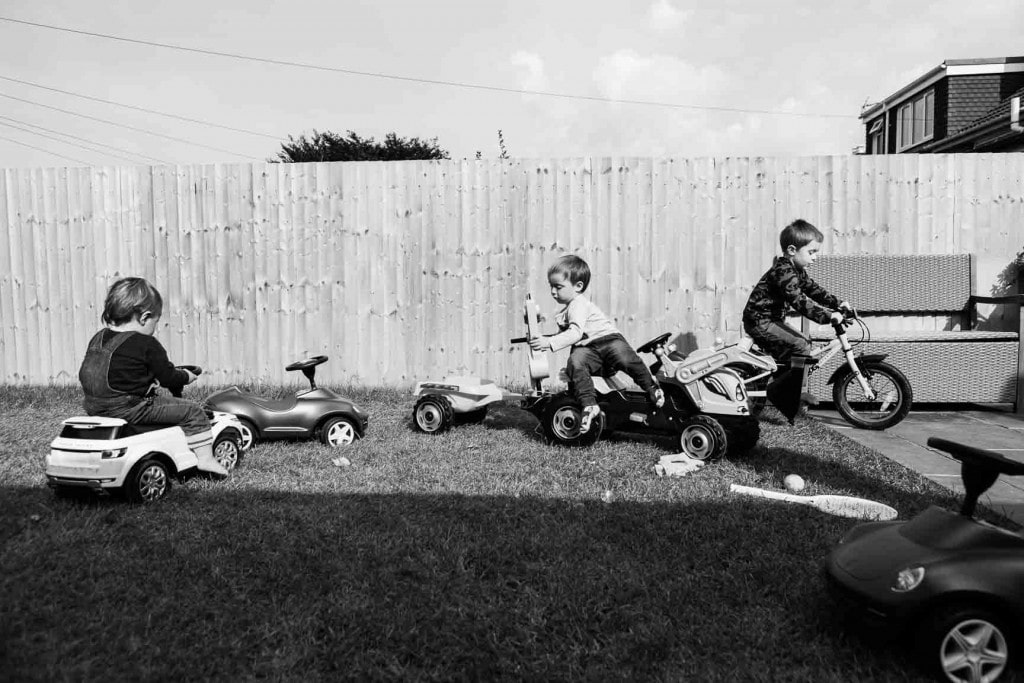 Three young brothers play in their garden on ride-ons