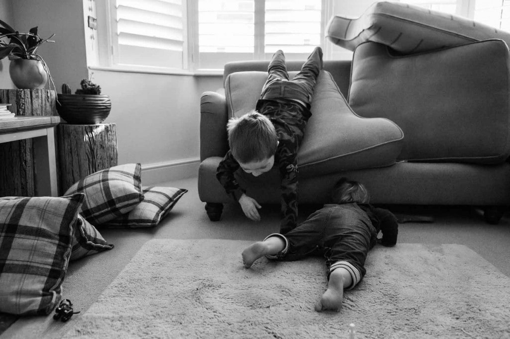 Two young brothers playing on and in their sofa
