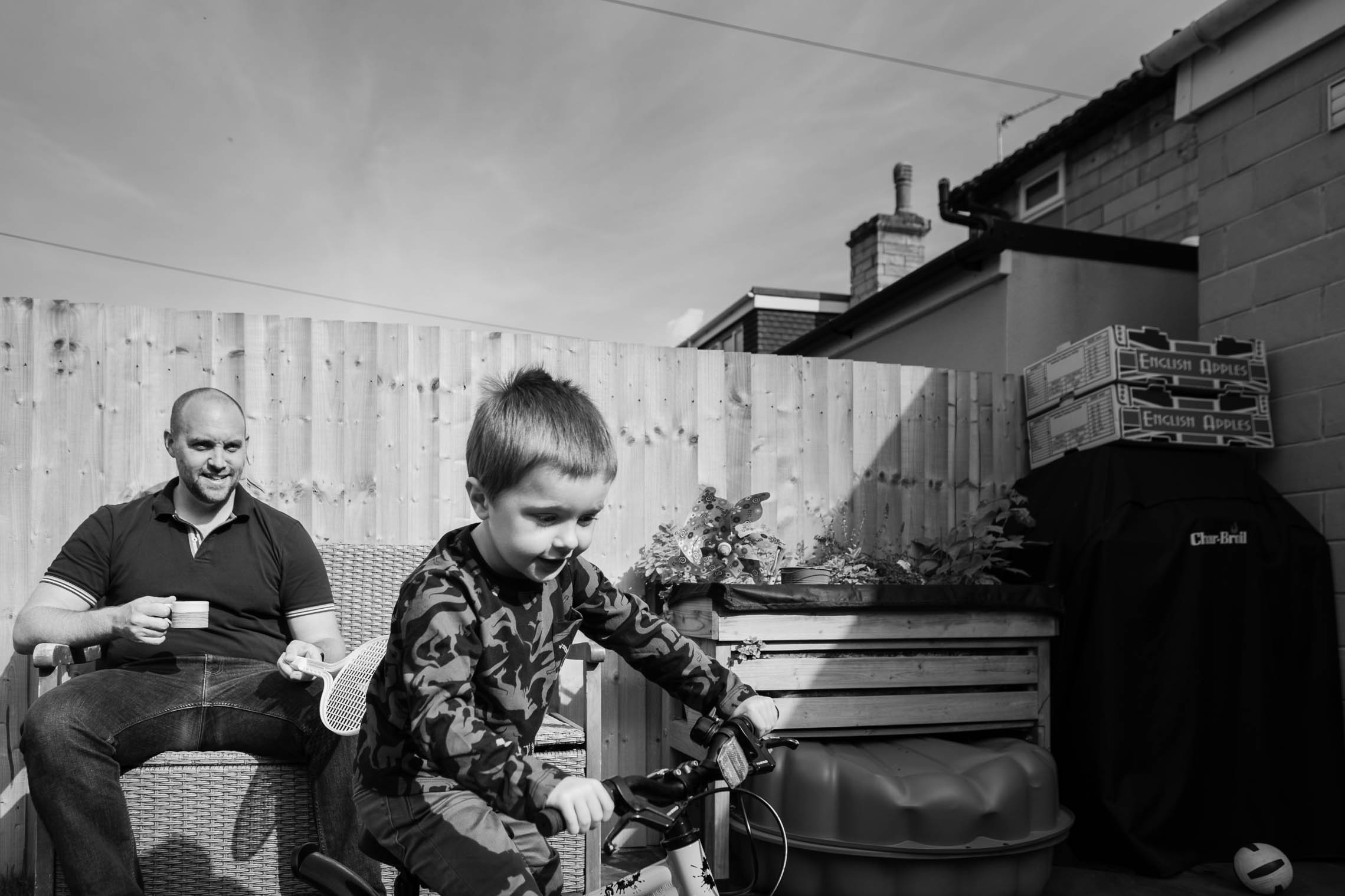 Little boy playing on his bike whilst Dad watches | Bath Family Photography