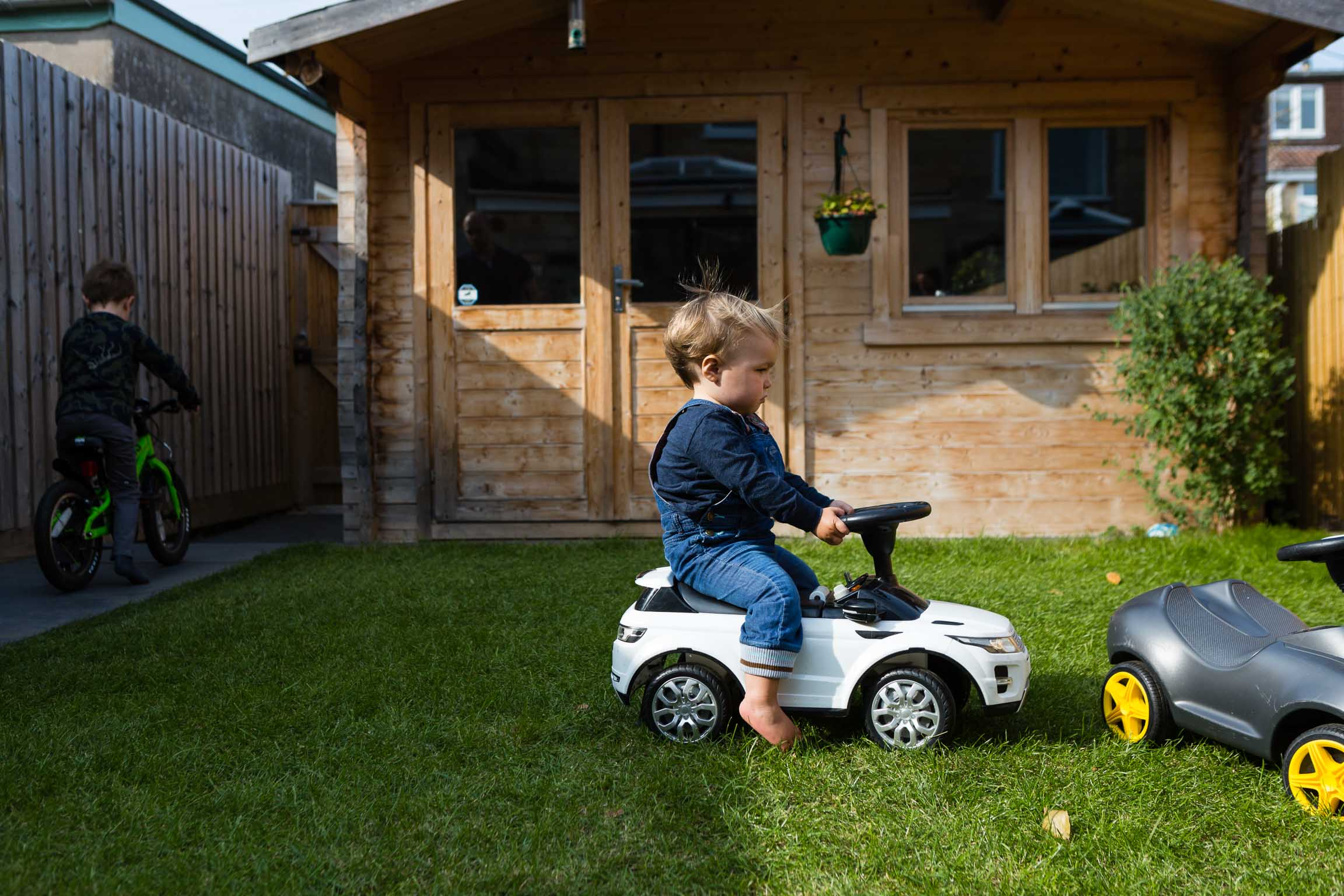 Little boy sat on his toy car in garden
