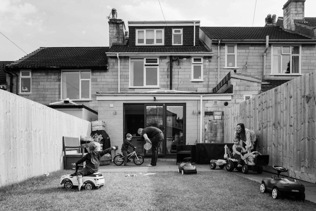View of family playing in garden with their house behind them - Bath