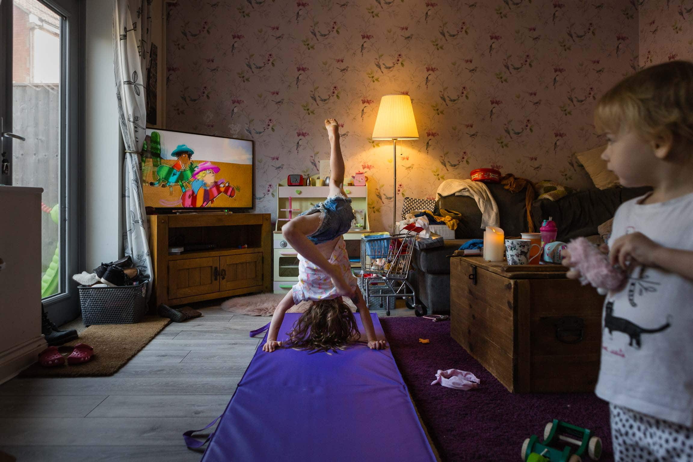 Little girl doing hand stand in living room | Bath Family Photography