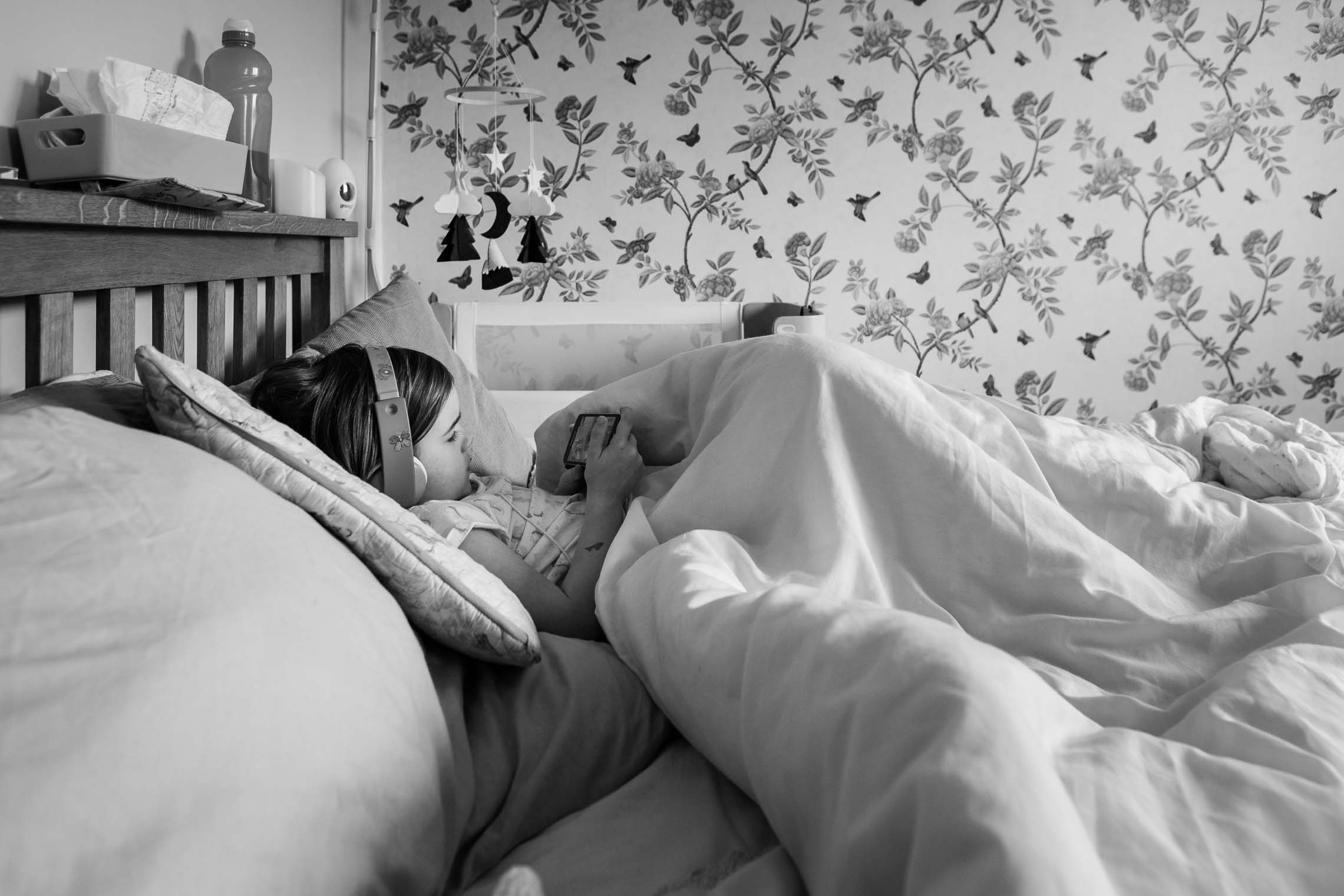 Little girl sits in bed watching phone | Bath Family Photography