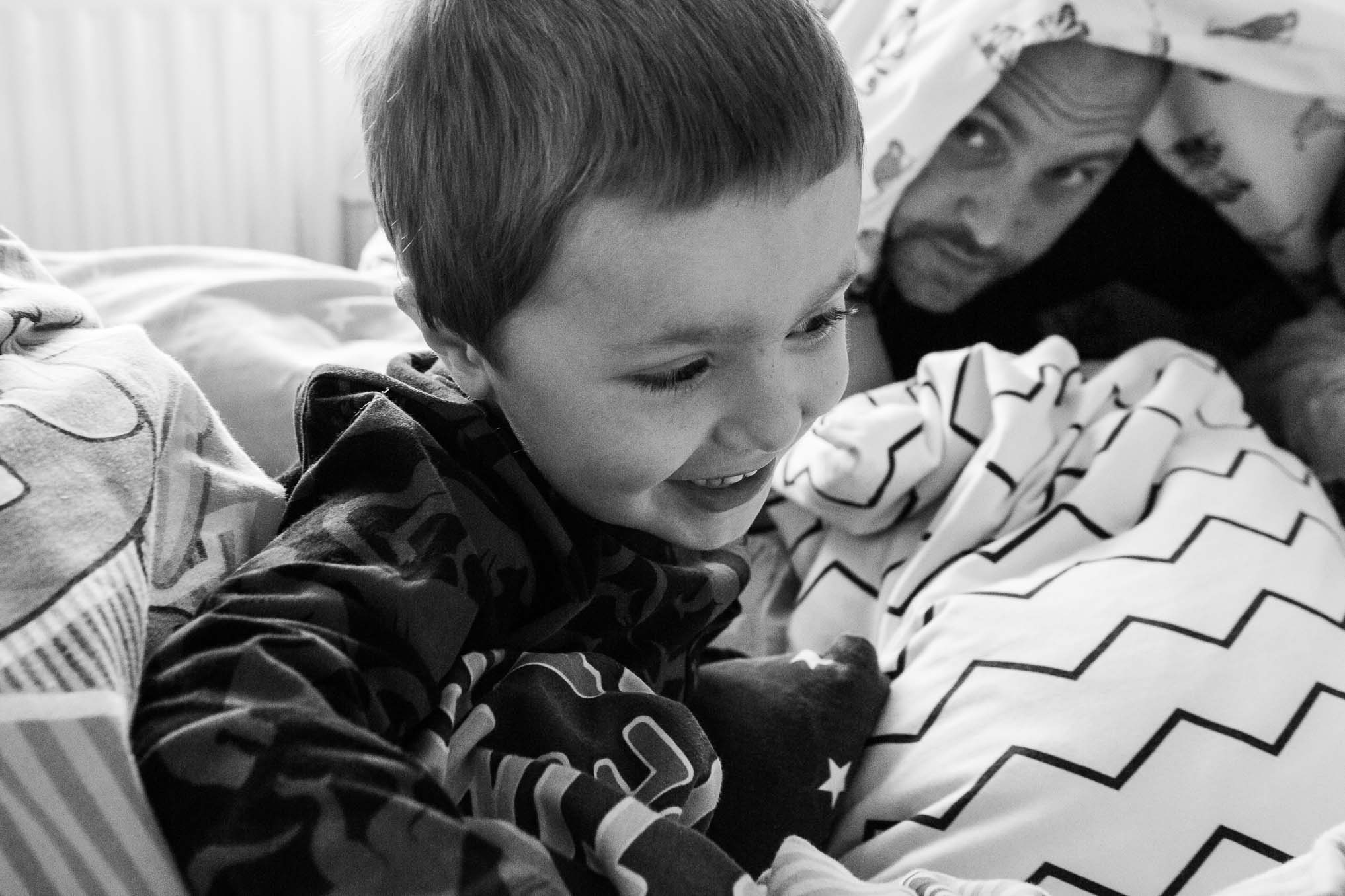 Little boy in foreground with Dad playing boo under duvet in background
