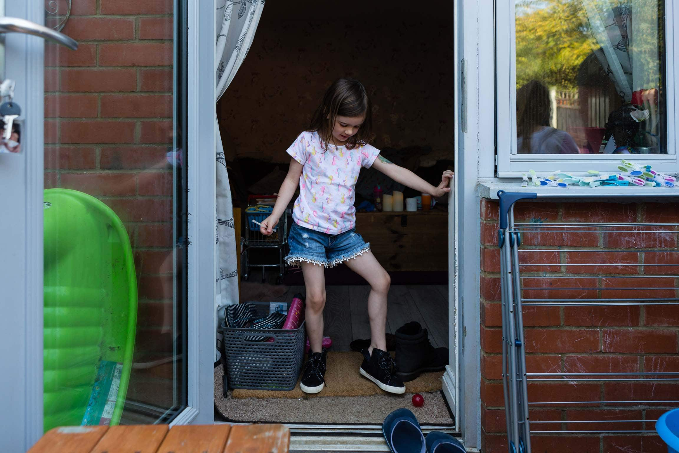 Young girl putting shoes on in doorway | Bath Family Photography