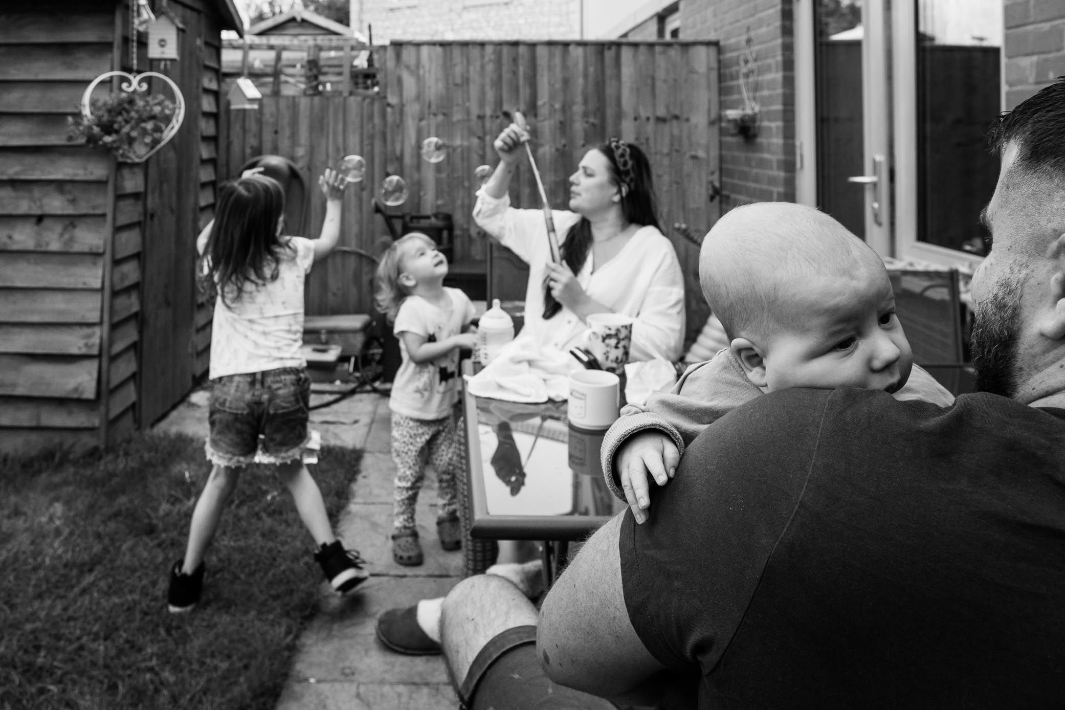 View of family playing in garden with bubbles | Bath Family Photography