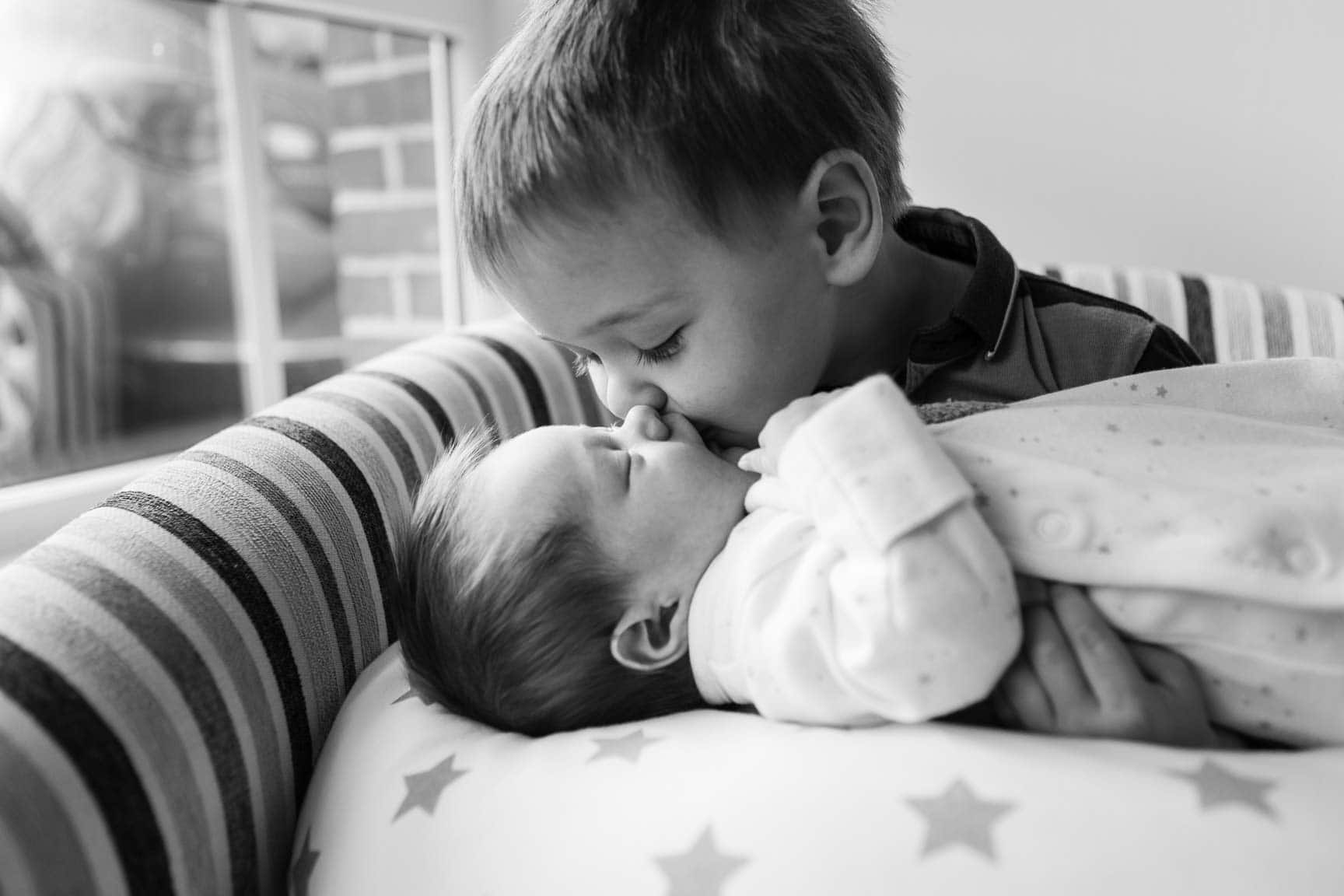 Big brother kisses baby sister